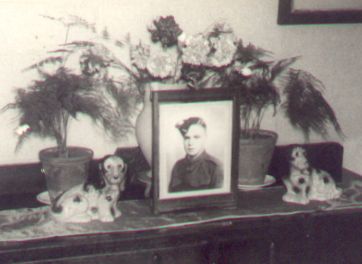 Archive image of framed photograph of Sydney on sideboard surrounded by flowers.