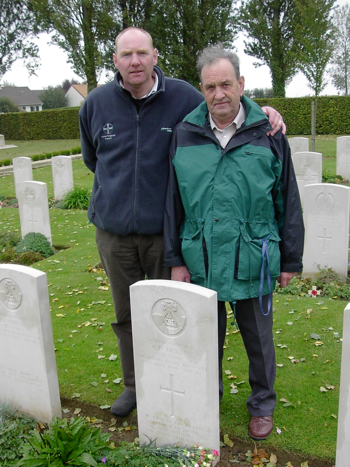 Geoffreys grave stone with Roger Bryan - great nephew - and Richard Bryan - nephew - standing next to each other behind it.