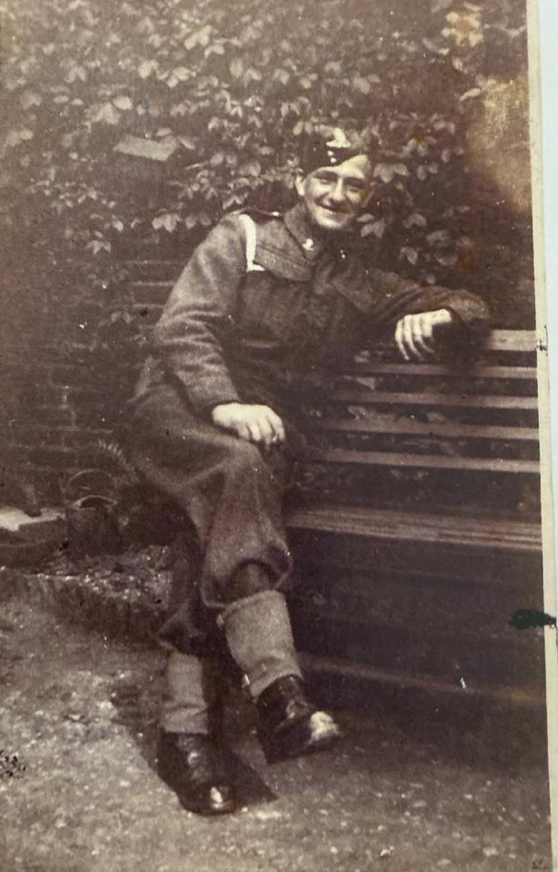 Thomas Warby in uniform sitting outside on a bench