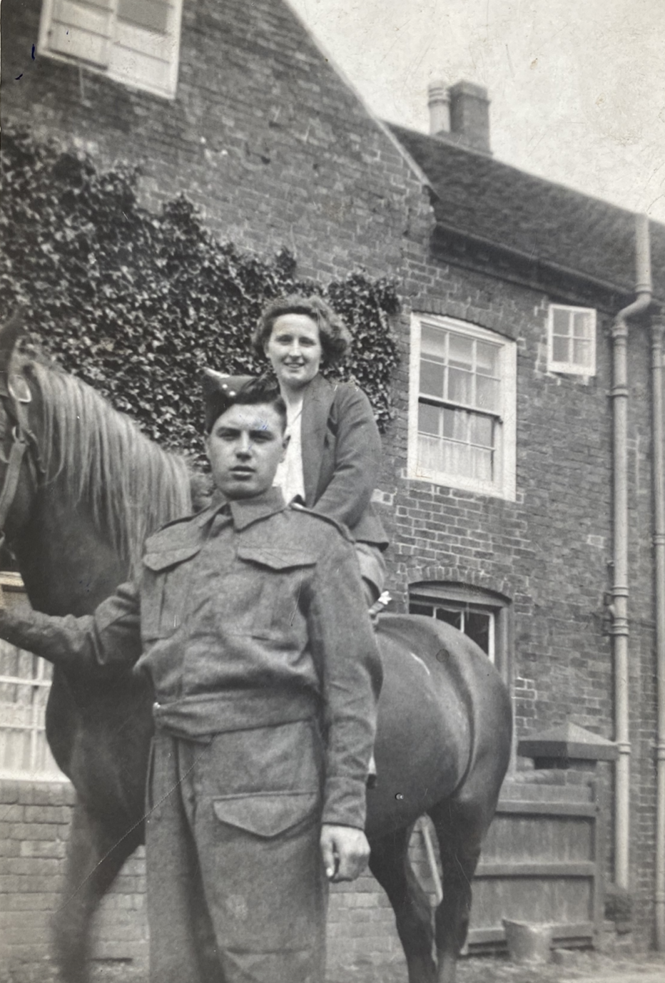 Photo of Tom standing next to woman on horseback, taken on the farm where he worked.