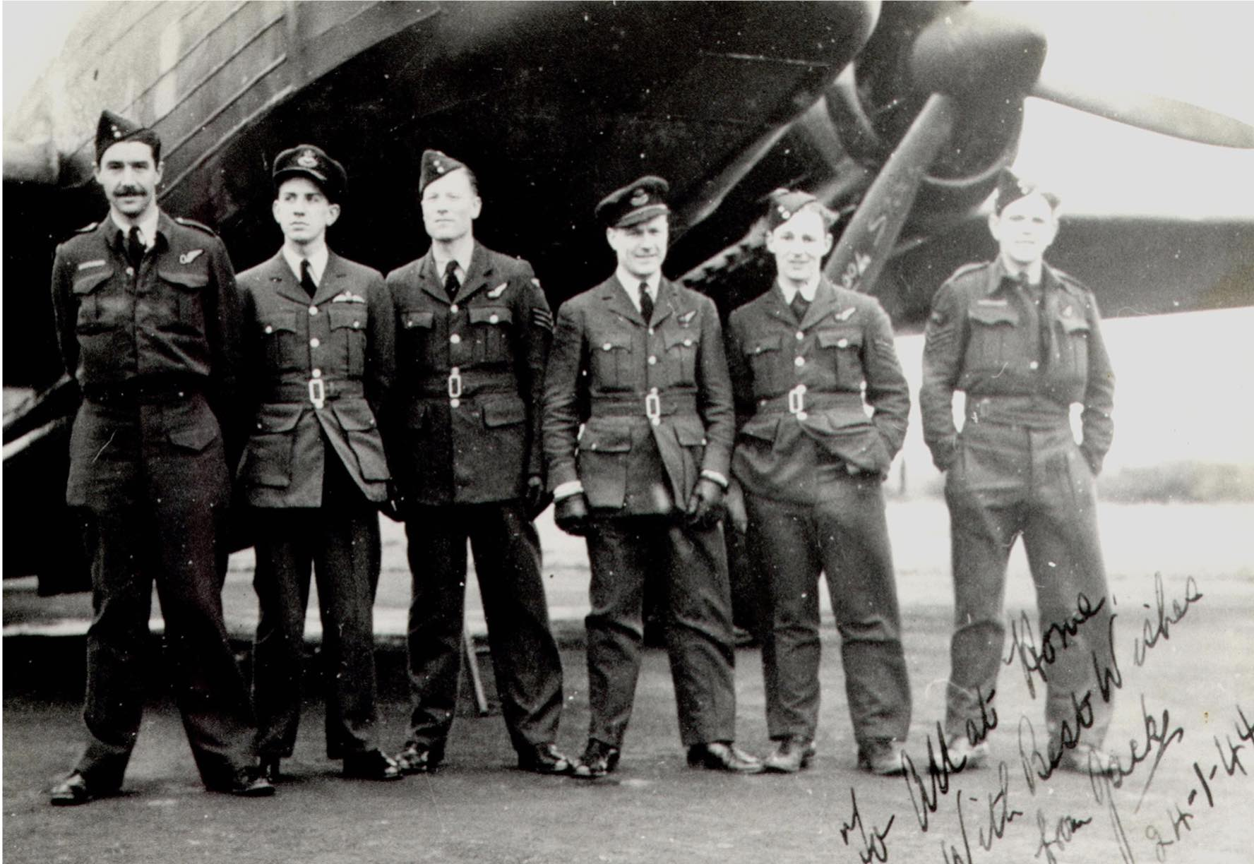 The photograph shows Jack, second from the left on a bomber conversion course prior to converting to the Lancaster. The aircraft is a Wellington bomber and several of the aircrew joined up with Jack on 115 Sqn. Extreme left is his observer. The photo is signed 'All at home, with best wishes from Jack. 24.1.44.'