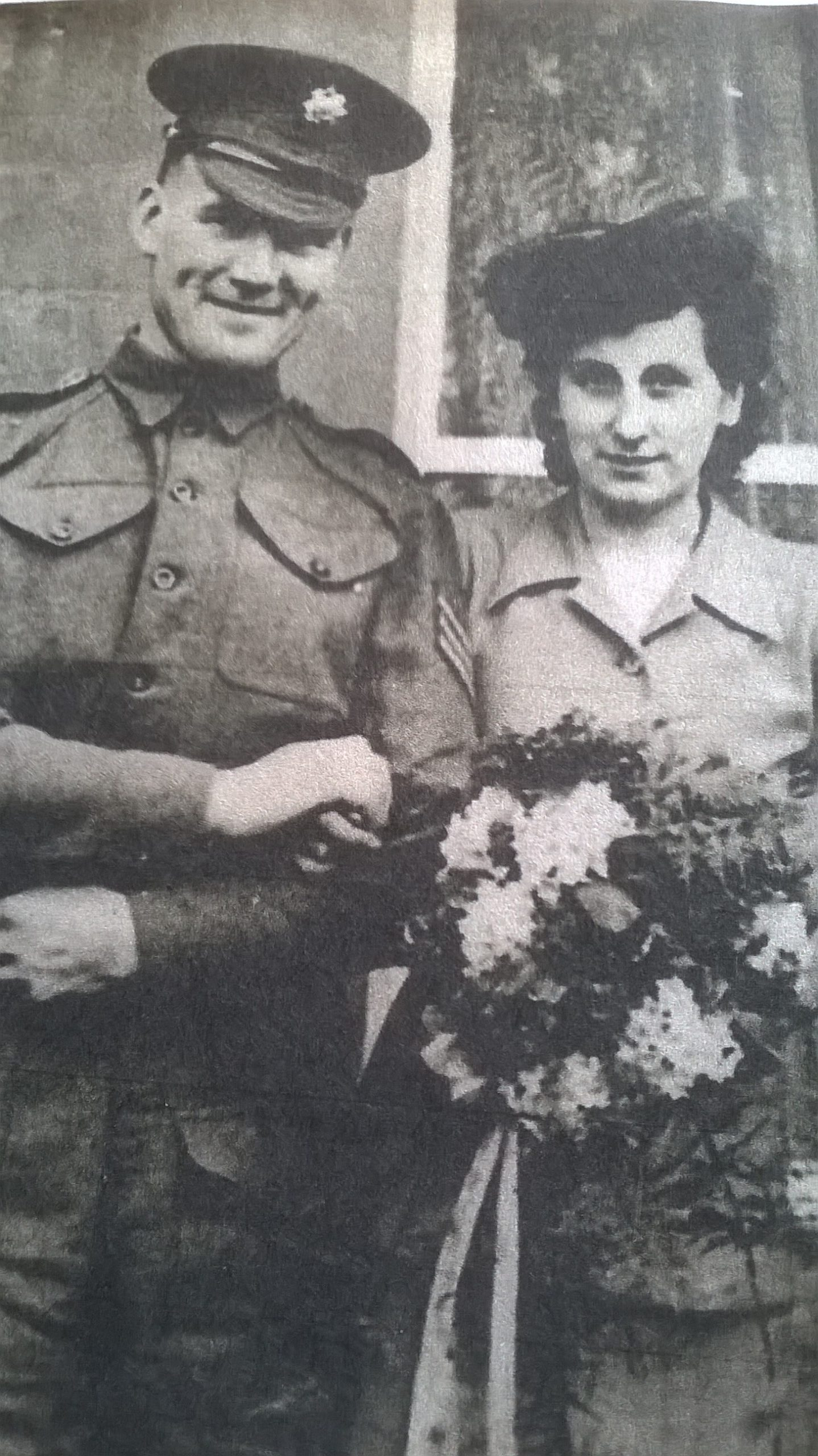 Andrew and Prue pictured on their wedding day. Andrew in uniform and Prue holding a bouquet of flowers.